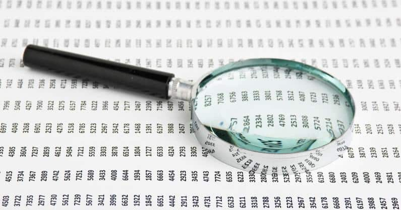 Photo of a magnifying glass laid on a sheet of codes