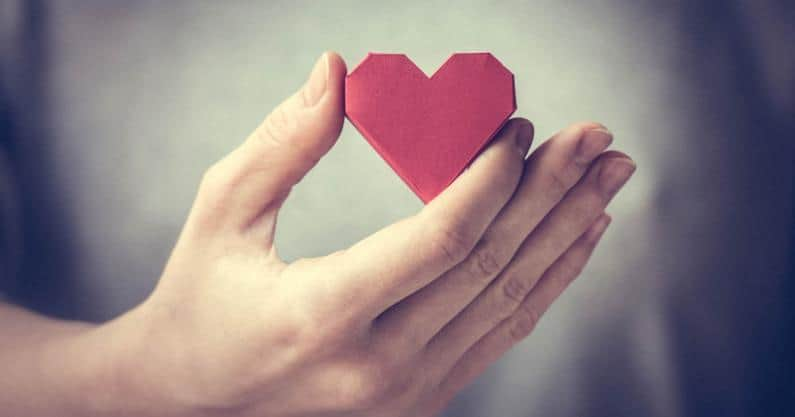 Photo of hand holding a cut-out paper heart
