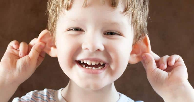 Portrait photo of young boy holding his ears out