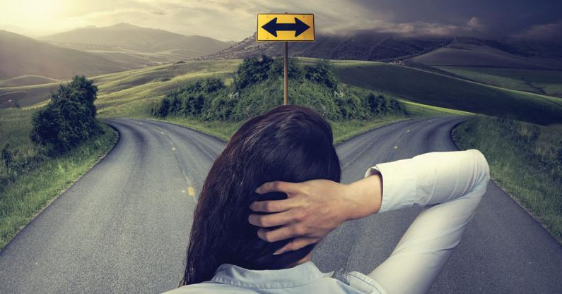 Photo of the back of female audiologist faced with 2 different road directions