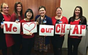 """Group of women holding up group of signs that read """"We Love Our CH-AP"""""""