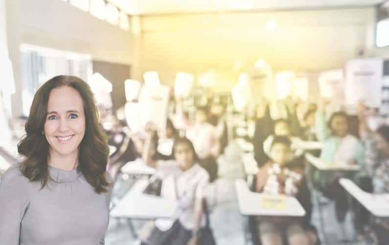 Image of Dana Suskind in front of a blurred classroom full of students