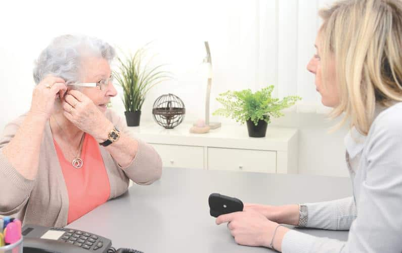 Photo of elderly patient being fitted with a hearing aid by an audiologist