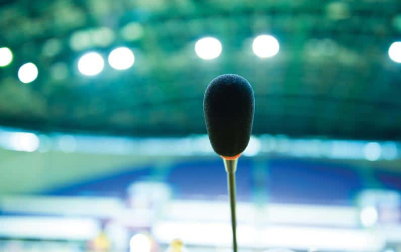 Close-up photo of public speaking microphone in front of blurred room of people
