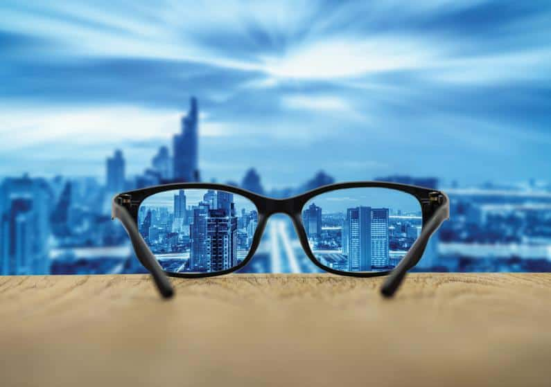 Close-up of glasses on a window ledge with the glasses showing clear view of city and the city in the background is blurry