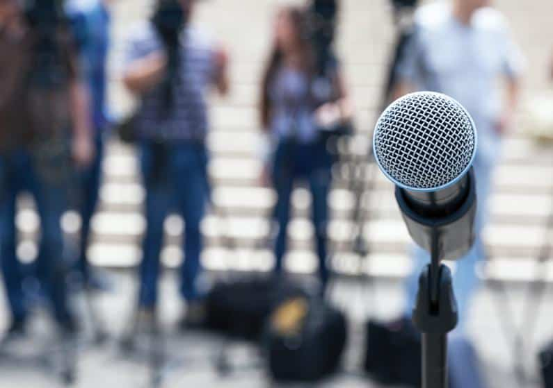 Photo of public speaking with close-up of microphone