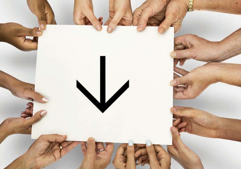 Close-up photo of hands holding sign with arrow pointing downward