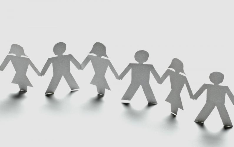 Photo of paper cut-outs of diverse people holding hands