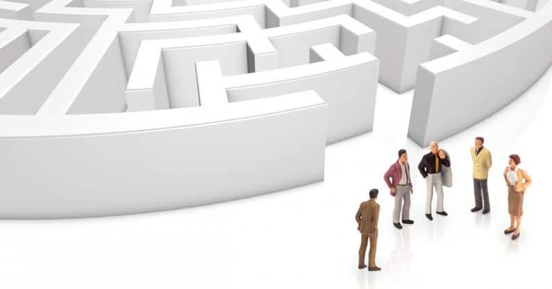 Image of a circular maze with a group of business figures having a discussion