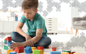 Autistic Boy playing with blocks with an overlay of puzzel pieces