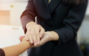 A close up photo of someone holding someone else's hand for comfort and support