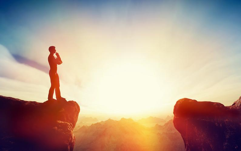 Man standing on cliff at sunrise
