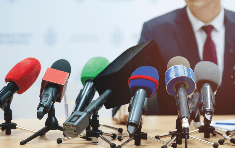 photo of man in front of microphones for news briefing