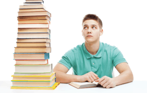 Photo of male student reading with large stack of books next to him