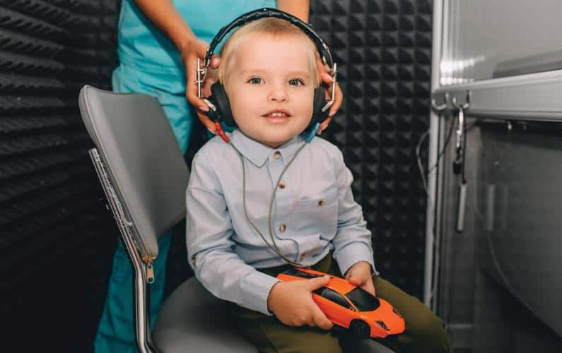 Photo of toddler having headphones placed on head by audiologist to get hearing test