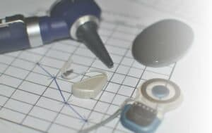 Photo of otoscope, hearing exam form, hearing aid, and cochlear implant
