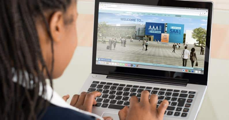 Close-up photo of audiologist on laptop with the AAA21 Virtual conference website on the screen