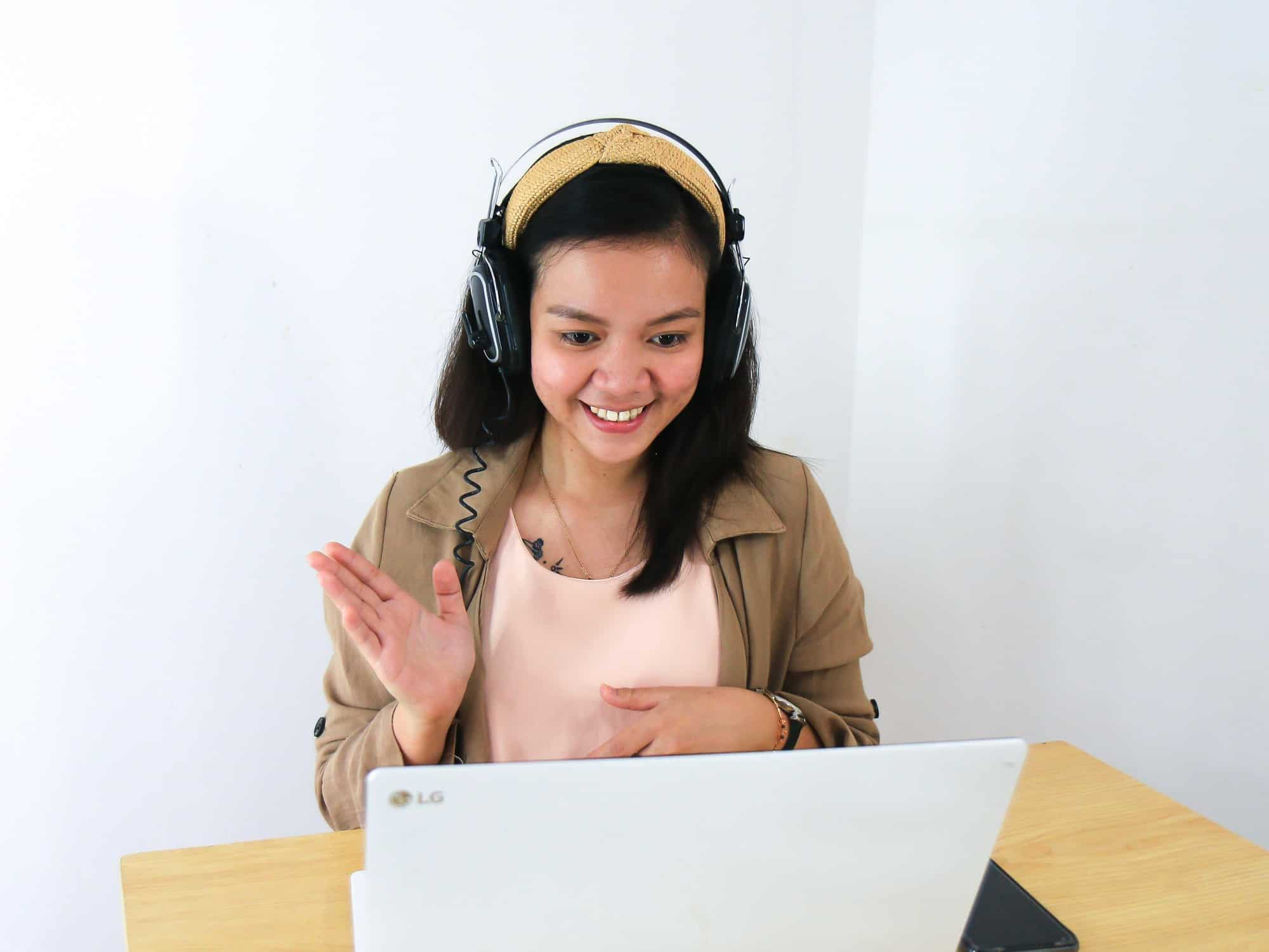 Girl using headphones and watching a webinar on a laptop