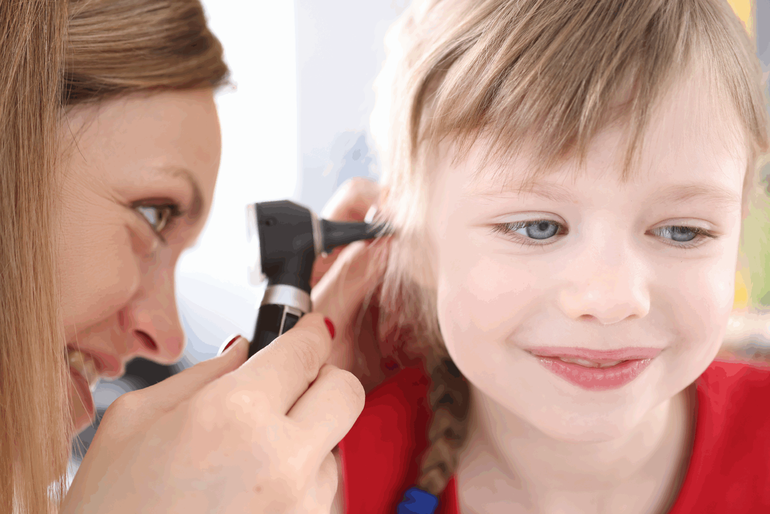 Audiologist looking at ear