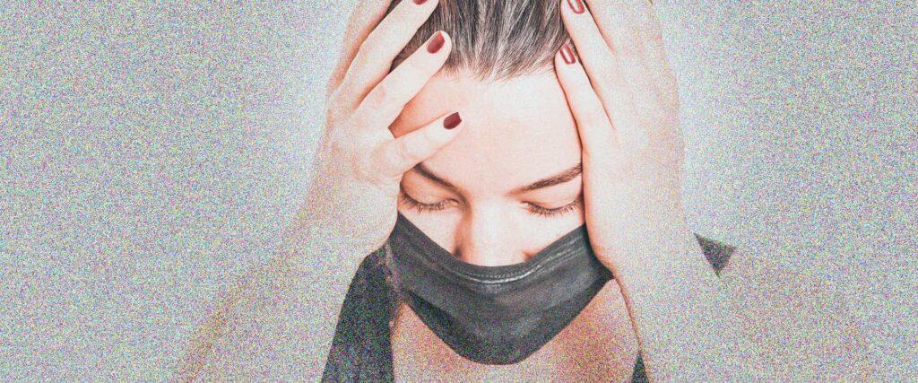 Close-up photograph of young masked woman with vertigo