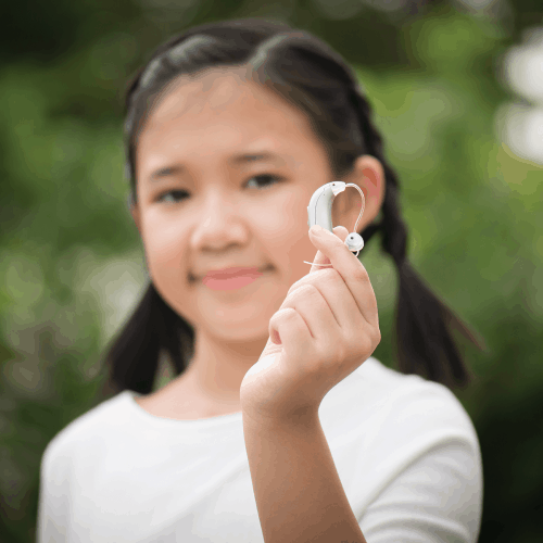 Out-of-focus image of an asian girl holding up a hearing aid