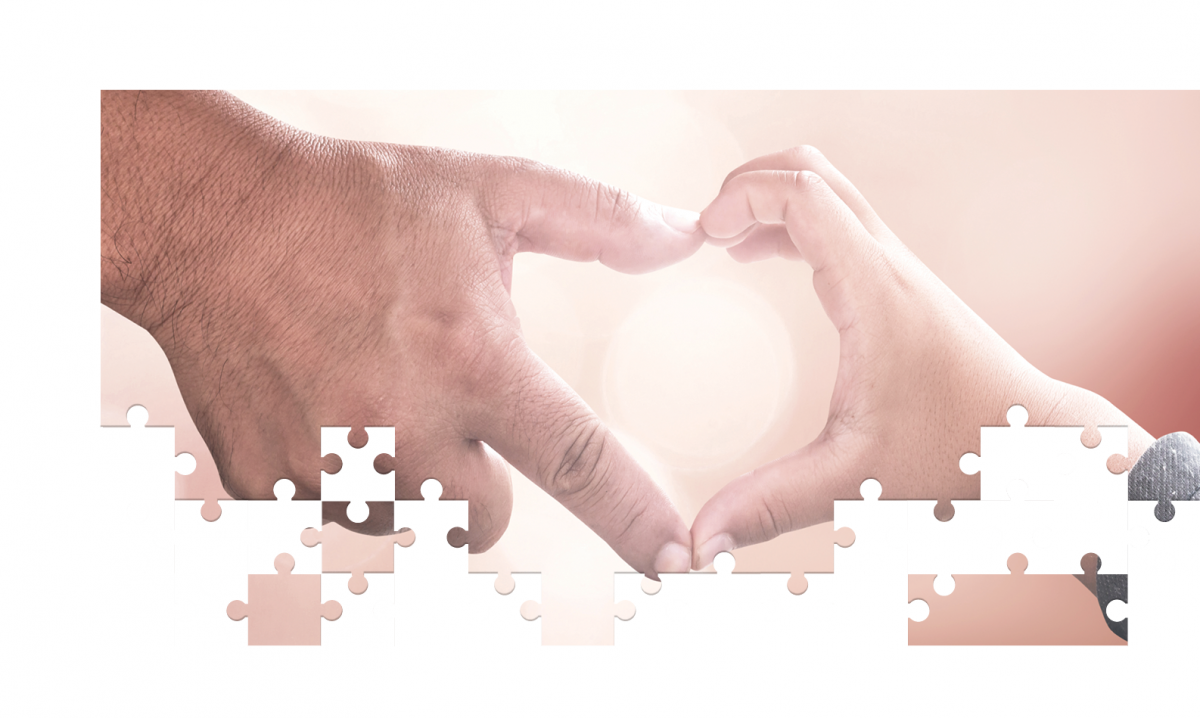 Hands forming heart between parent and child