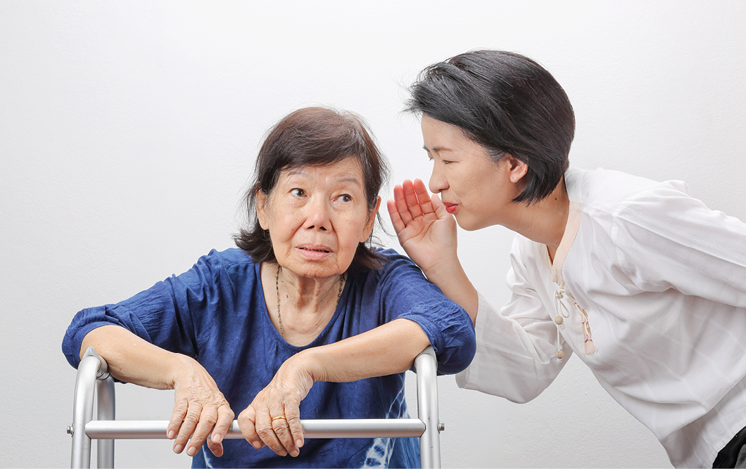 Older hard-of-hearing asian woman and her daughter image