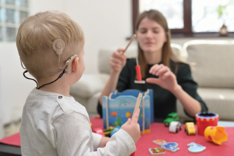 Adult interacting with young child with cochlear implant